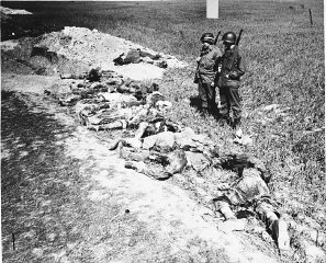 American soldiers look at the exhumed bodies of prisoners...