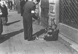 A Warsaw ghetto resident gives money to two children...