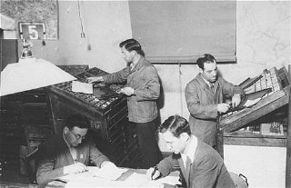 Jewish refugees work on a newspaper at Zeilsheim displaced...