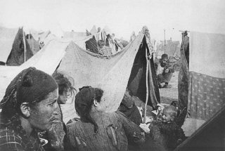 Armenian families next to makeshift tents in a refugee...
