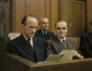 Defendant Alfried Krupp (left) reads a document while seated in the dock at a session of the Krupp Trial in Nuremberg.