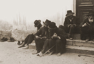 Jewish men sitting on the steps of a synagogue.