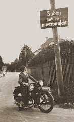 "A motorcyclist reads a sign stating ""Jews are..."