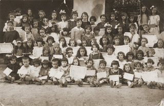 Group portrait of children holding their diplomas at...