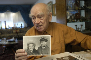 Norman Salsitz holds a photograph of himself and Am...