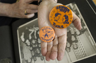 Regina Gelb holds buttons from her high school days...