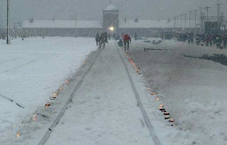 Candles mark the railway tracks leading to the Auschwitz...