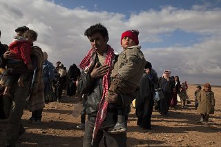 Refugees displaced by the violence in Syria walk to...