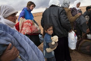 Refugees displaced by the violence in Syria wait at...