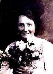 Formal portrait of Frieda Greinegger holding a bouquet...
