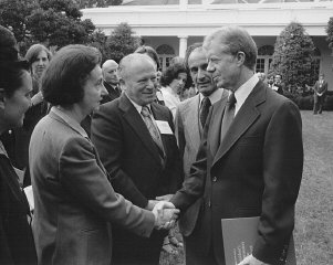 Vladka Meed shakes the hand of President Jimmy Carter at a White House Rose Garden ceremony marking the official presentation of the report of the US Holocaust Commission to the president by commission chairman Elie Wiesel (second from right, with Benjamin Meed, center). Washington, DC, September 27, 1979.
