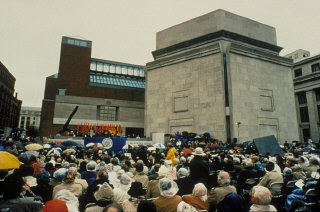 A large crowd fills Eisenhower Plaza during the dedication ceremony of the United States Holocaust Memorial Museum. Flags of the liberating divisions form the backdrop to the opening ceremony. Washington, DC, April 22, 1993.