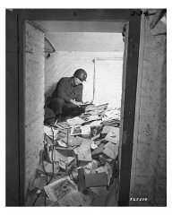 A US soldier inspects piles of Nazi books, including...
