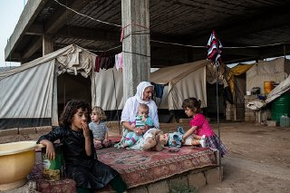 An elderly Yazidi woman tends to young children beside...
