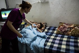 A mother checks on her sick daughter inside the container...