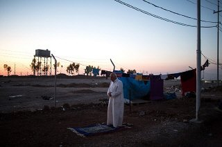 A Sunni man from Mosul, Iraq, prays as the sun sets...
