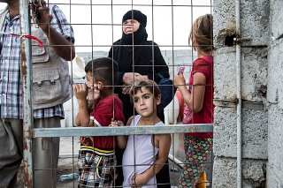 Displaced Iraqis wait for food distribution at an internally...