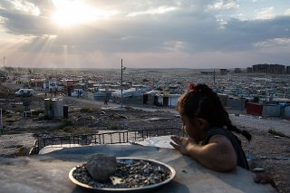 A Syrian girl looks over the Domiz refugee camp outside...