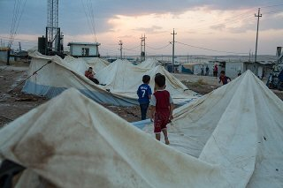 Refugee boys from Syria play on old tents in the Domiz...