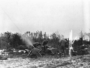 Mortar men of the 754th Tank Battalion fire an 81mm...