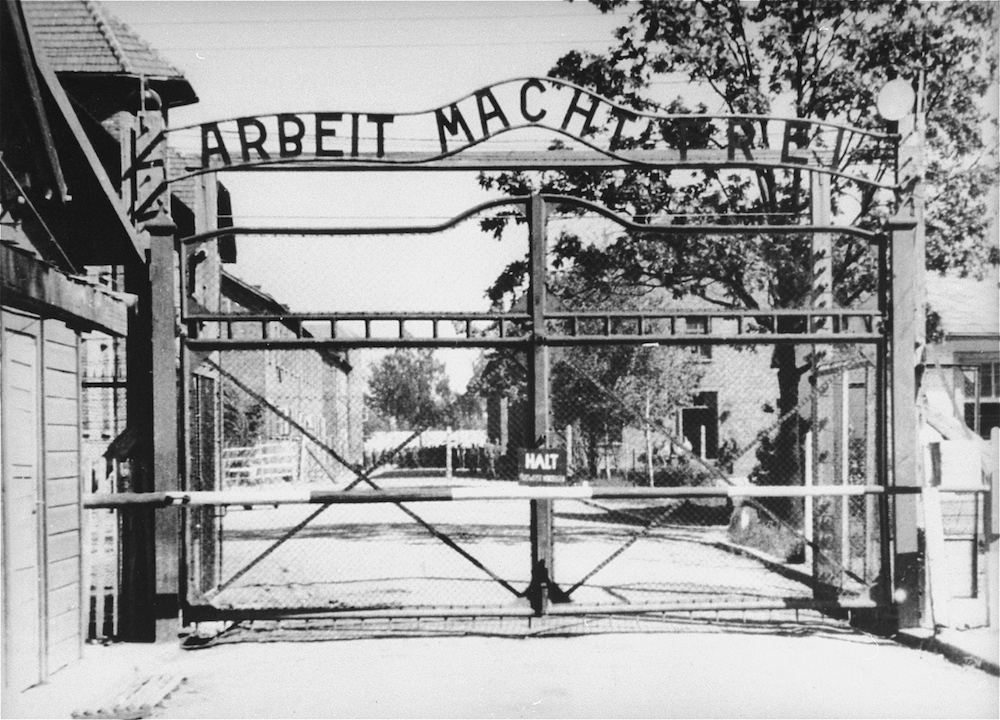 "The entrance to the main camp at Auschwitz, bearing the motto ""Arbeit Macht Frei."""