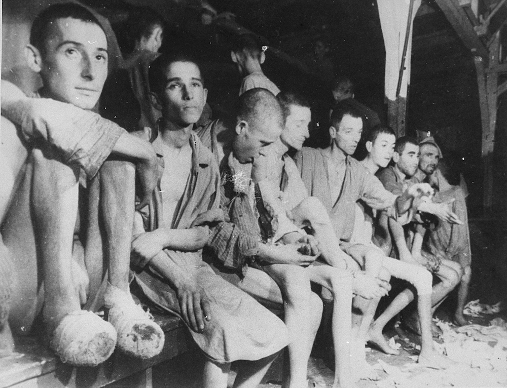 Wounded and sick survivors, Russians, Poles, and Jews, sitting on a bench inside a barracks in Buchenwald concentration camp.