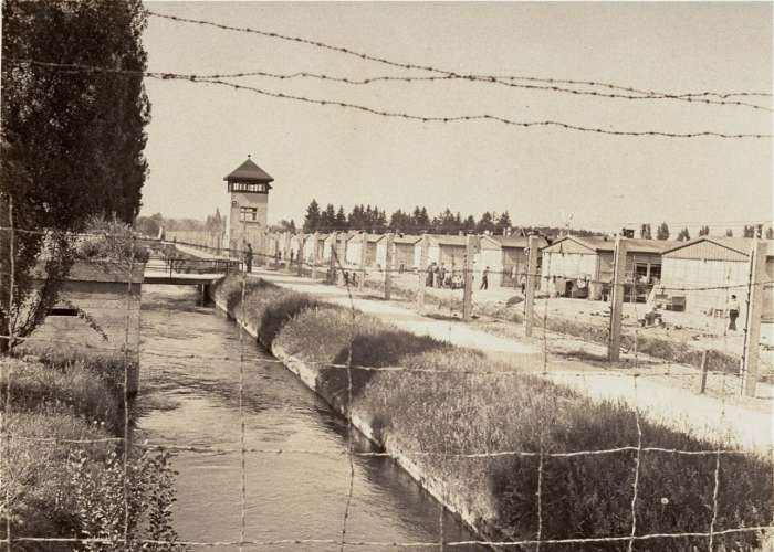 View of a section of the newly liberated Dachau concentration camp as seen through the barbed-wire fence. Dachau, Germany, May 1945. <i>US Holocaust Memorial Museum, courtesy of Merle Spiegel</i>