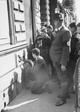 A crowd of Viennese children looks on as a Jewish youth is forced to paint the word