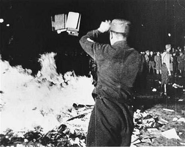 "A member of the SA throws confiscated books into the bonfire during the public burning of ""un-German"" books on the Opernplatz in Berlin, May 10, 1933."