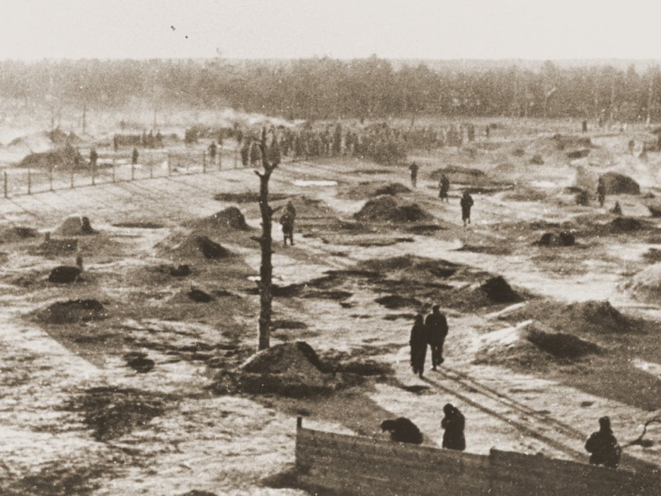 Soviet prisoners stand among the underground holes that served as their only shelter at the Wietzendorf POW camp.