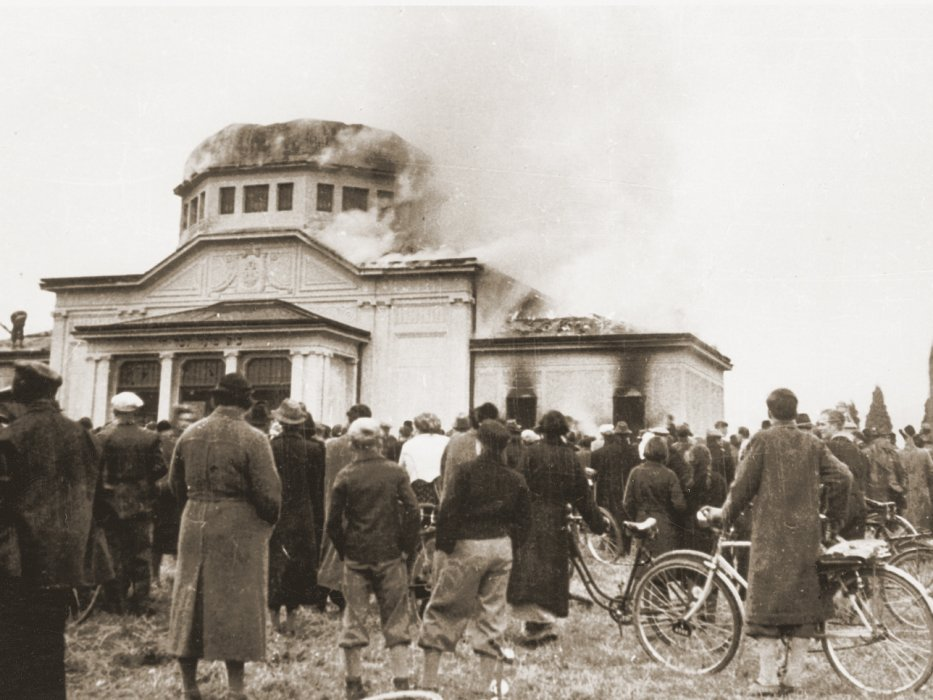 Local residents watch the burning of the ceremonial hall at the Jewish cemetery in Graz.
