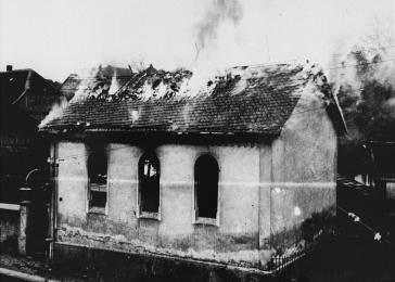 On the morning after Kristallnacht, local residents watch as the synagogue is destroyed by fire. The local fire department prevented the fire from spreading to a nearby home but did not try to limit the damage to the synagogue. Ober Ramstadt, Germany. November 10, 1938.