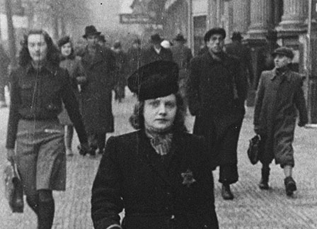 A woman walks down the street with a Jewish star visible on her coat