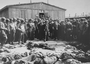 While on a tour of the newly liberated concentration camp, General Dwight Eisenhower and other high-ranking US Army officers view the bodies of prisoners who were killed during the evacuation of Ohrdruf. <i>US Holocaust Memorial Museum, courtesy of National Archives and Records Administration, College Park, MD</i>