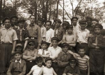 Group portrait of members of the Hashomer Hadati Zionist youth organization on an outing in the woods.