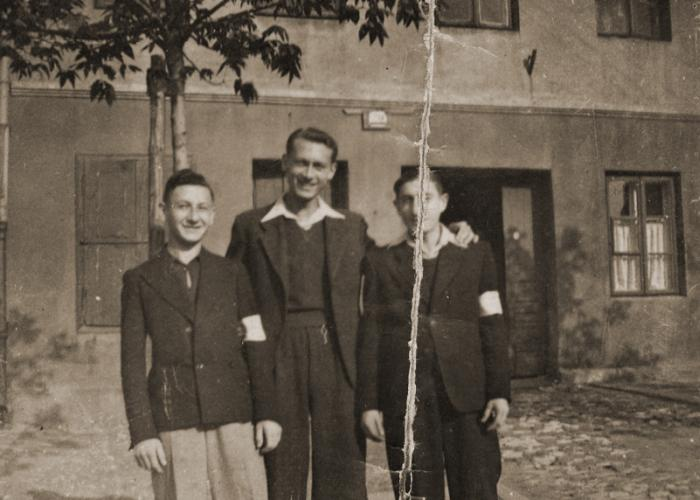 Three Jewish youth pose outside in the Dabrowa Gornicza ghetto.