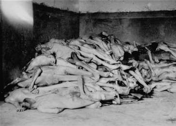 The bodies of former prisoners are piled in the crematorium mortuary in the newly liberated Dachau concentration camp. Dachau, Germany, April 29, 1945. <i>US Holocaust Memorial Museum, courtesy of George McDaniel III</i>