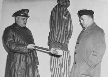 During a US Army chaplain inspection of the newly liberated Buchenwald concentration camp, G. Bromley Oxnam (right), the Methodist bishop of New York and President of the Federated Council of Churches of Christ in America, views a demonstration of how prisoners were tortured in Buchenwald. <i>US Holocaust Memorial Museum, courtesy of National Archives and Records Administration, College Park, MD</i>