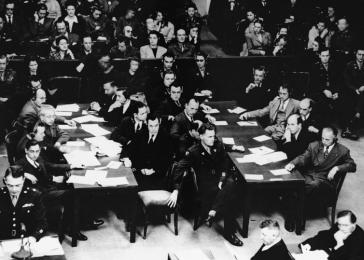The prosecution team during the Doctors Trial, including Chief of Counsel Brigadier General Telford Taylor (standing, lower left) and Chief Prosecutor James M. McHaney (seated behind Taylor). The Trial was held in Nuremberg, Germany, from December 9, 1946, to August 20, 1947.
