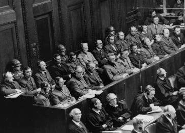 Defendants seated under guard in the dock behind the defense counsel during the Doctors Trial, which was held in Nuremberg, Germany, from December 9, 1946, to August 20, 1947.