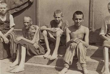 Emaciated survivors sit outside a barracks in the newly liberated Dachau concentration camp. —US Holocaust Memorial Museum, courtesy of Frank Manucci, David J. Levy, Kathleen Quinn, Theodore A. Kane Jr.