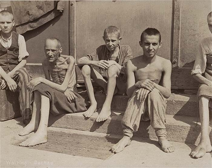 A group of emaciated survivors sit outside a barracks in the newly liberated Dachau concentration camp.