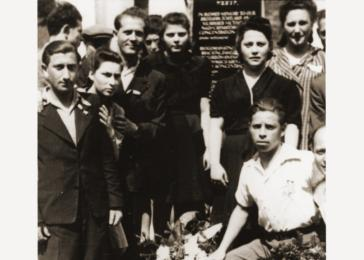 Jewish DPs from the New Palestine displaced persons camp gather around a memorial erected to the Jewish victims of the Nazis.