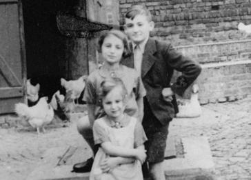 Gisela Berg, her sister Inge, and their cousin Harvey Meyer pose outside on their family farm prior to their emigration from Germany. Pictured are  The Meyer family left for the U.S. on the day this photograph was taken.