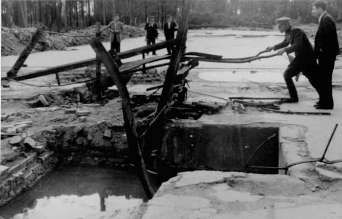 Members of an international commission of inquiry view the ruins of the crematorium in Auschwitz-Birkenau. March 1945.