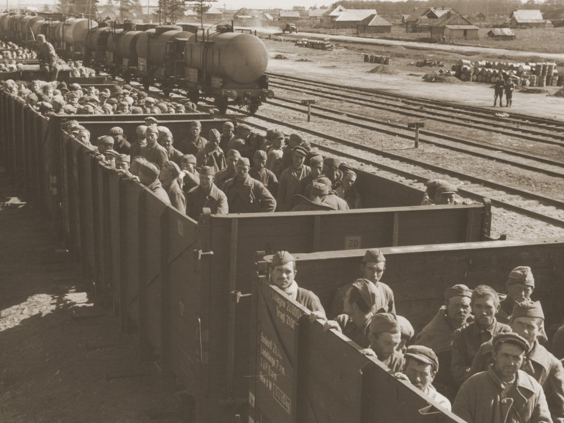 A train full of Soviet POWs, under German guard, passing through an unidentified rail yard.