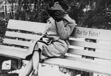 "A woman sits on a park bench marked ""Only for Jews."" Austria, ca. March 1938. <i>US Holocaust Memorial Museum, courtesy of Wiener Library Institute of Contemporary History</i>"