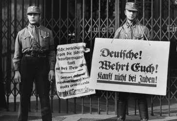 "SA men with boycott signs block the entrance to a Jewish-owned shop. The signs read: ""Germans, defend yourselves against the Jewish atrocity propaganda, buy only at German shops!"" and ""Germans! Defend yourselves! Do not buy from Jews!"" Berlin, Germany, April 1, 1933."
