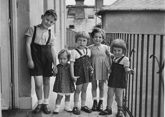 Gyorgy Pick (left), with his cousin, Clara Kornhauser (second from the left) and non-Jewish neighbors pose on the balcony of an apartment in Budapest.