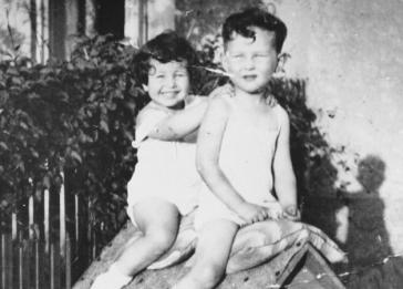 Two Jewish cousins sit atop a dog house in the yard of their grandparents' home on Dorozsmai Street in Budapest. Pictured are Gyorgy Pick (five years) and his cousin, Agnes Szalai (five years).